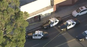 Police converge at an apartment complex in Long Beach after a man was found dead and a woman was injured in a shooting on Sept. 14, 2016. (Credit: KTLA)