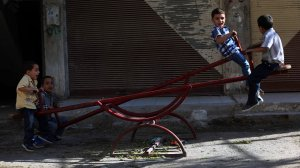 Syrian boys play on a see-saw in the rebel-held town of Arbin as they celebrate the Muslim Eid al-Adha holiday on Sept. 13, 2016. (Credit Amer Almohibany/AFP/Getty Images)