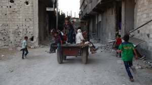 Syrian children play in the street in the rebel-controlled town of Hamouria as they celebrate the third day of the Al-Adha Eid Muslim holiday on the second day of an internally backed ceasefire on Sept. 14, 2016. (Credit: Abd Doumany/AFP/Getty Images)