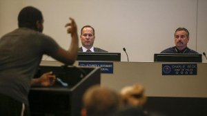 The Los Angeles Police Commission's inspector general, Alex Bustamante, and LAPD Chief Charlie Beck listen as a protester speaks at a commission meeting on Oct. 3, 2016. (Credit: Mark Boster / Los Angeles Times)