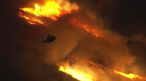 A helicopter is seen battling a brush fire at the Aliso Canyon gas facility near Porter Ranch on Oct. 18, 2016. (Credit: KTLA)