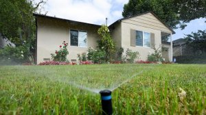 Sprinklers water the front lawn of a house on Zelzah Avenue in Encino earlier this year. (Credit: Michael Owen Baker/Los Angeles Times)