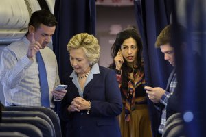 Democratic presidential nominee Hillary Clinton looks at national press secretary Brian Fallon's smart phone while on her plane with aide Huma Abedin and traveling press secretary Nick Merrill at Westchester County Airport Oct. 3, 2016, in White Plains, New York. (Credit: BRENDAN SMIALOWSKI/AFP/Getty Images)