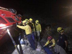 Fire personnel rescue a missing woman from an overturned Hummer in Adelanto in an image posted to the San Bernardino County Fire Department's Facebook page on Oct. 29, 2016.