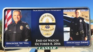 "Palm Springs officers Jose ""Gil"" Vega and Lesley Zerebny are seen in a billboard outside the Palm Springs Convention Center. (Credit: KTLA)"