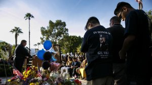 "Family members of slain police officers Jose ""Gil"" Vega bow their heads in prayer as they attend a vigil on Oct. 9, 2016. (Credit: Marcus Yam / Los Angeles Times)"