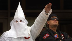 In this file photo, a hooded Klansman raises his left arm while another looks into the crowd during a Ku Klux Klan rally Dec. 16, 2000 in Illinois. (Credit: Tim Boyle/Newsmakers)