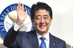 Japan's Prime Minister Shinzo Abe waves to well-wishers prior to boarding a government plane at Tokyo's Haneda on November 17, 2016. (CREDIT: KAZUHIRO NOGI/AFP/Getty Images)