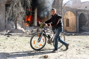 A Syrian youth pushes his bicycle past a burning house on Nov. 19, 2016, following a reported air strike on a rebel-held neighborhood of Aleppo. (Credit: Ameer Alhalbi/AFP/Getty Images)