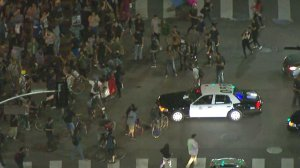 A protest flows around an LAPD vehicle in downtown L.A. on Nov. 10, 2016. (Credit: KTLA)