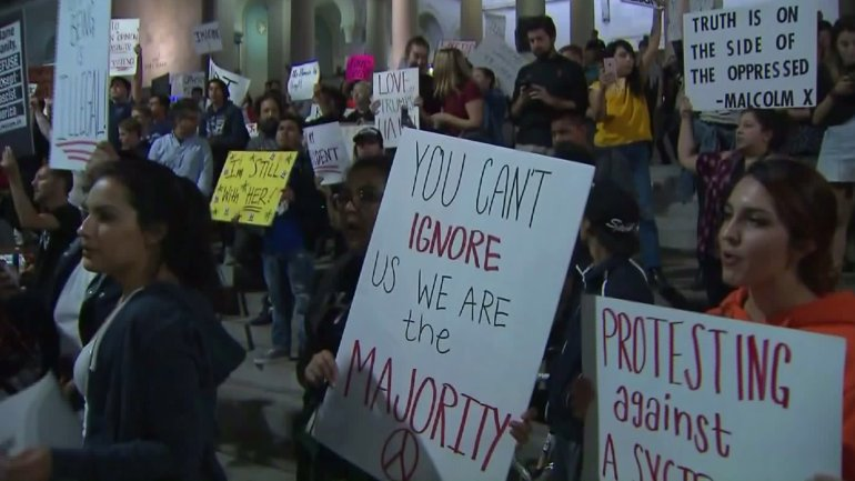 Protesters hold signs on the steps of L.A. City Hall on Nov. 10, 2016. (Credit: KTLA)