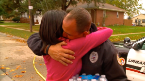A woman hugs an Urbandale, Iowa, police officer hours after another officer was fatally shot on Nov. 2, 2016. (Credit: KCCI via CNN)