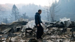 Trevor Cates, walks through the smoldering remains of the fellowship hall of his church, the Banner Missionary Baptist Church as he inspects damage after a wildfire November 29, 2016 in Gatlinburg, Tennessee.  (Credit: Brian Blanco/Getty Images)