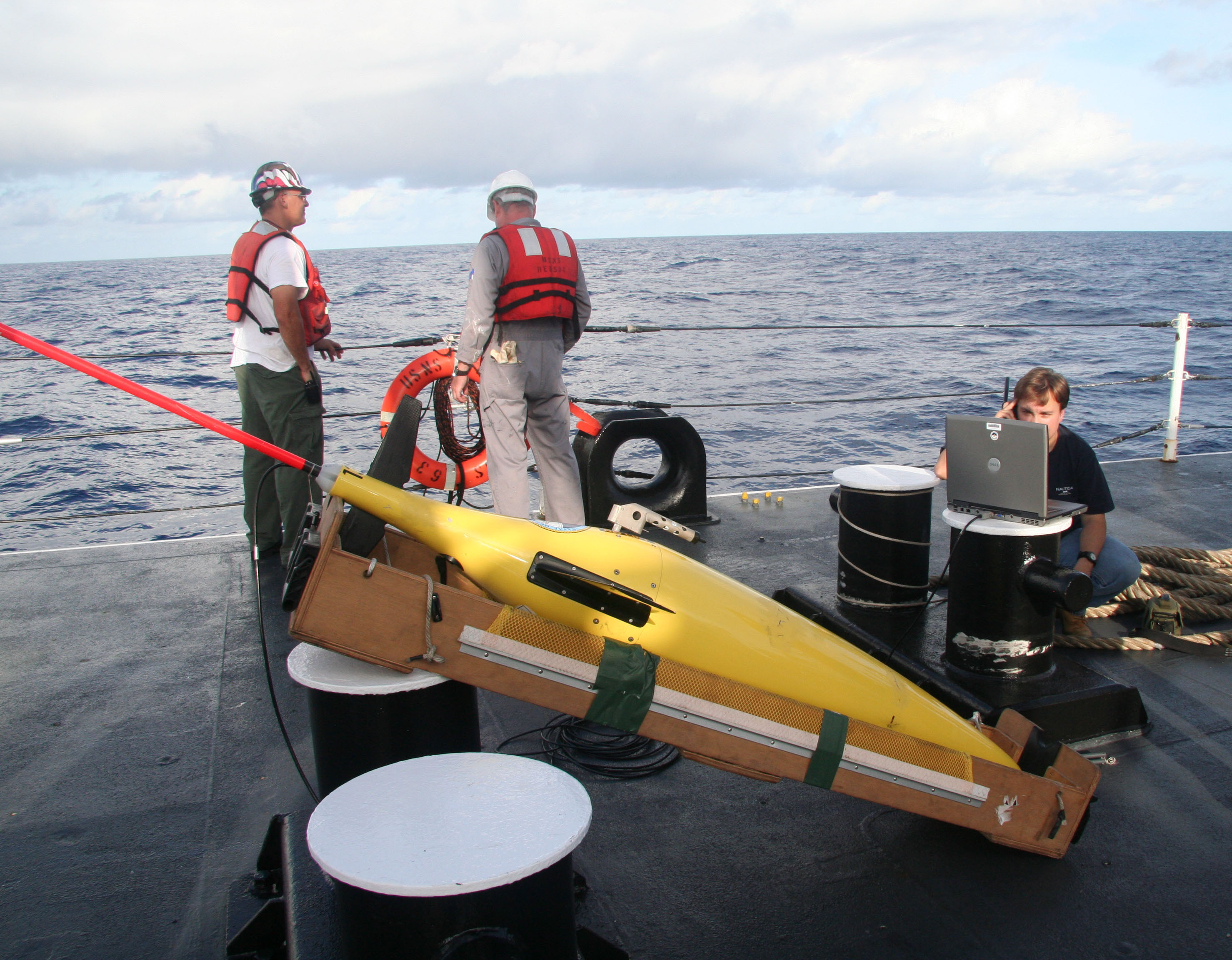 An oceanographer from the Naval Oceanographic Office, right, establishes a satellite connection before launching a seaglider unmanned underwater vessel from the Military Sealift Command oceanographic survey ship USNS Henson on March 24, 2010. (Credit: U.S. Navy / Petty Officer 2nd Class Lily Daniels)