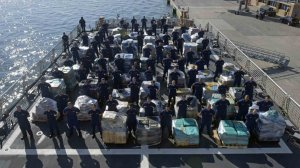 Members of the Coast Guard Cutter Hamilton crew stand next to approximately 26.5 tons of cocaine Dec. 15, 2016 aboard the cutter at Port Everglades Cruiseport in Fort Lauderdale, Florida. (Coast Guard photo by Petty Officer 3rd Class Eric D. Woodall)