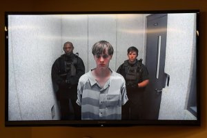 In this image from the video uplink from the detention center to the courtroom, Dylann Roof appears at Centralized Bond Hearing Court June 19, 2015, in North Charleston, South Carolina. (Credit: Grace Beahm-Pool/Getty Images)
