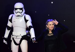 """Carrie Fisher poses with a stormtrooper at the opening of the European premier of """"Star Wars: The Force Awakens"""" in central London on Dec. 16, 2015. (Credit: LEON NEAL/AFP/Getty Images)"""