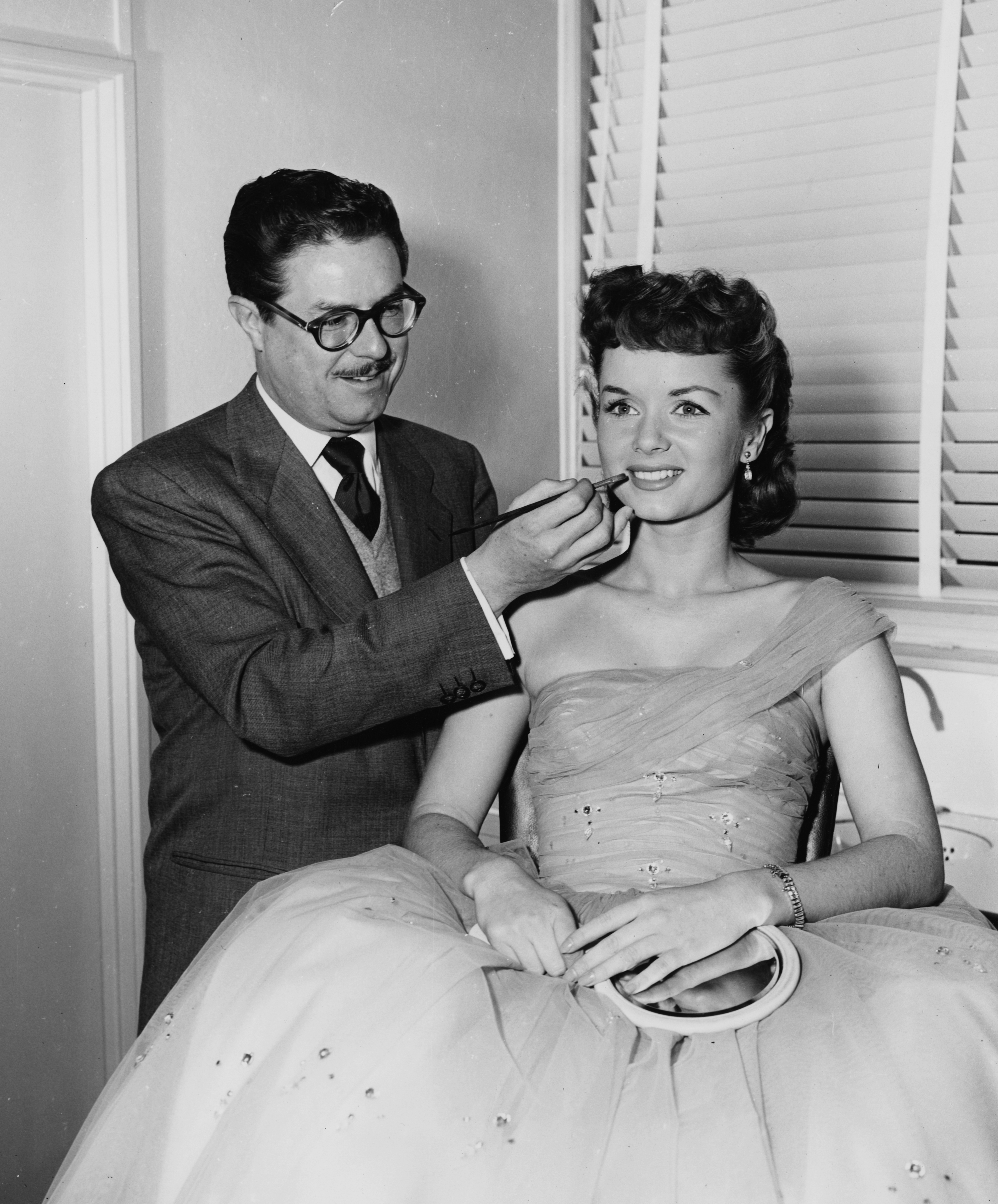 Makeup artist William J. Tuttle is seen applying lipstick on actress Debbie Reynolds, circa 1965. (Credit: Keystone/Hulton Archive/Getty Images)
