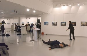 This picture taken on Dec. 19, 2016, shows Andrey Karlov, the Russian ambassador to Ankara, lying on the floor after being shot by a gunman, right, during an attack during a public event in Ankara. (Credit: STRINGER/AFP/Getty Images)