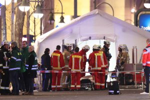 Rescue workers gather outside a tent in the area after a truck drove through a Christmas market on Dec. 19, 2016, in Berlin, Germany. (Credit: Sean Gallup/Getty Images)