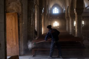 A man sweeps dust off seating in preparation for the Christmas Day mass at the Mar Hanna Church on Dec. 22, 2016 in Mosul, Iraq.(Credit: Chris McGrath / Getty Images)