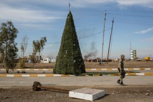 An NPU fighter walks in front of a large Christmas tree erected on the main road on Dec. 22, 2016 in Mosul, Iraq. (Credit: Chris McGrath / Getty Images)
