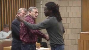 Rakeem Jones, left, shakes hands with James Franklin McGraw before the pair hugged in court on Dec. 14, 2016. (Credit: CNN)