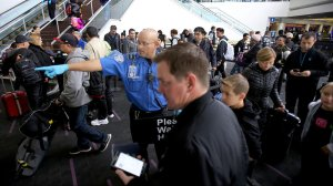 A TSA agent guides holiday travelers through a security checkpoint in Terminal 2 at LAX on Thursday, one of the busiest travel days of the year. (Credit: Luis Sinco / Los Angeles Times)