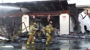 Fire crews continue to put out hot spots after a fire burned through a strip mall in Monterey Park on Dec. 15, 2016. (Credit: KTLA)