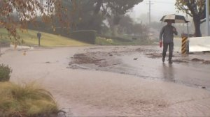 A man walks along a rainy street with mudflows in an undated file photo. (Credit: KTLA)