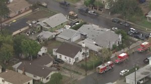Police and fire vehicles surround a home in San Fernando where one person was apparently dead and at least one other person was injured in a shooting on Dec. 23, 2016. (Credit: KTLA)