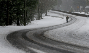 Running Springs resident Sean Benton walks along Holiday Lane as snow flurries hit the area in a 2013 photo. (Credit: Luis Sinco / Los Angeles Times)
