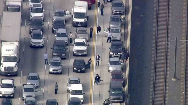 Some motorists got out of their car during a massive traffic jam on the 210 Freeway that was triggered when the roadway was closed for a police investigation on Dec. 7, 2016. (Credit: KTLA)