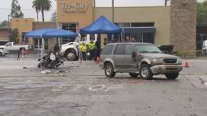 A Pomona officer's motorcycle and the SUV it collided with remain at the scene on Jan. 10, 2017. (Credit: KTLA)