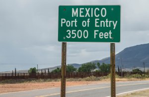 Mexico port of entry highway sign on Highway 92 in Naco Arizona with border fence in the background. (Credit: iStock/Getty Images Plus)