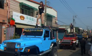 This picture taken on Jan. 3, 2017, shows pole dancers performing on top of jeeps during the funeral procession of former Chiayi City county council speaker Tung Hsiang in Chiayi City, southern Taiwan. (Credit: STR / AFP / Getty Images)
