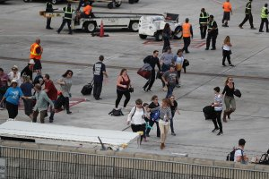People seek cover on the tarmac of Fort Lauderdale-Hollywood International airport after a shooting took place near the baggage claim on January 6, 2017 in Fort Lauderdale, Florida. . (Credit: Joe Raedle/Getty Images)