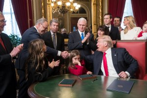 President Donald Trump shakes hands with Senate Minority Leader Chuck Schumer, D-N.Y, as he is joined by the Congressional leadership and his family while he formally signs his cabinet nominations into law, in the President's Room of the Senate, at the Capitol in Washington, Jan. 20, 2017. (Credit: J. Scott Applewhite - Pool/Getty Images)