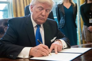 President Donald Trump signs an executive order in the Oval Office at the White House in Washington, DC, on January 24, 2017. (Credit: NICHOLAS KAMM/AFP/Getty Images)