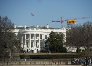 """Greenpeace protesters unfold a banner reading """"Resist"""" from atop a construction crane behind the White House Jan. 25, 2017, in Washington, D.C. The banner, flying high enough to be seen from the White House, is in opposition to the policies of President Donald Trump. (Credit: SAUL LOEB/AFP/Getty Images)"""