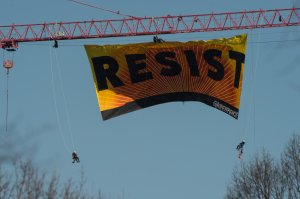 """Greenpeace protesters hang from a banner reading """"Resist"""" from atop a construction crane behind the White House Jan. 25, 2017, in Washington, D.C. (Credit: NICHOLAS KAMM/AFP/Getty Images)"""