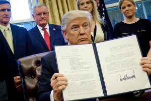 President Donald Trump holds up one of the executive actions that he signed in the Oval Office on Jan. 28, 2017 in Washington, DC.  (Credit: Pete Marovich - Pool/Getty Images)