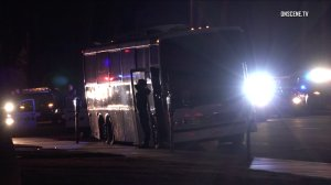 An individual exits a party bus with hands raised after the vehicle was pulled over in Huntington Beach on Jan. 7, 2017. (Credit: OnScene)