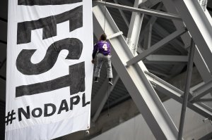 Protesters of the Dakota Access Pipeline unfurl a banner calling for the divestment of US Bank from the rafters during the second quarter of the Minnesota Vikings and Chicago Bears game on January 1, 2017. (Credit: Hannah Foslien/Getty Images)