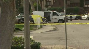 Police found two people shot to death inside a car that had crashed into a front yard in Pomona on Jan. 13, 2017. (Credit: KTLA)