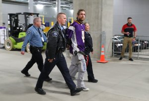 Police transport a protester after the Minnesota Vikings and Chicago Bears football game on January 1, 2017 at US Bank Stadium in Minneapolis, Minnesota. The protesters unfurled a banner in opposition to the Dakota Access Pipeline in the second quarter of the game. (Credit: Adam Bettcher/Getty Images)
