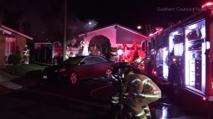 Firefighters remain at the scene of a fire at a Westminster home belonging to a woman who was later found dead in Newport Beach over the New Year weekend. (Credit: Southern Counties News)