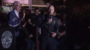 Whittier police Chief Jeff Piper, right, speaks at a vigil for Officer Keith Boyer while Whittier Mayor Joe Vinatieri, left, holds a candle on Feb. 20, 2017. (Credit: KTLA)