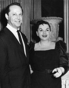 American singer and actress Judy Garland with her husband Sidney Luft at a reception in her honor at Londonderry House on Oct. 10, 1957. (Credit: Edward Miller / Keystone / Getty Images)