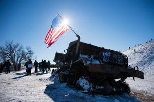 Activists and veterans pass a burnt out dump truck as they depart a police barricade on a bridge near Oceti Sakowin Camp on the edge of the Standing Rock Sioux Reservation on Dec. 4, 2016, outside Cannon Ball, North Dakota. (Credit: JIM WATSON/AFP/Getty Images)